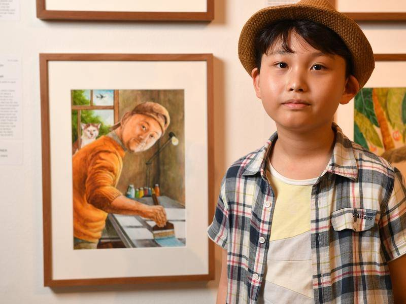 Ian Joseph Kim with the painting of his artist father that won him a Young Archie.